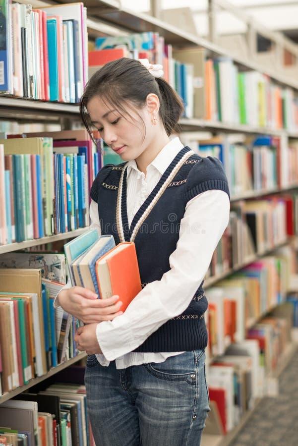 Mujer que sostiene los libros y que parece subrayada imagen de archivo