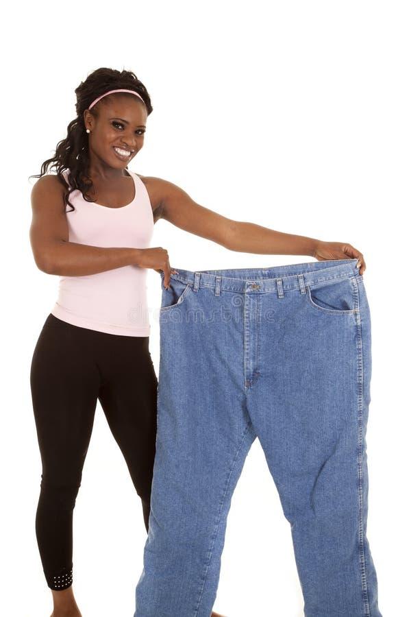 Mujer que sostiene los pantalones enormes fotos de archivo