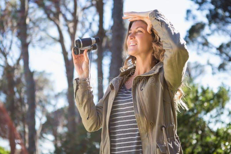 Mujer que sostiene los prismáticos imagen de archivo