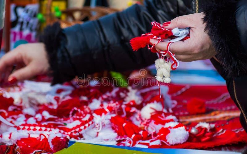 Mujer que sostiene martisor y martenica tradicionales rojos y blancos en su mano al aire libre foto de archivo