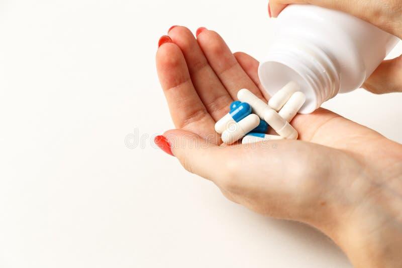 Mujer que sostiene p?ldoras a mano Concepto de la medicina y de la atenci?n sanitaria Mano que derrama las píldoras para el dolor imágenes de archivo libres de regalías