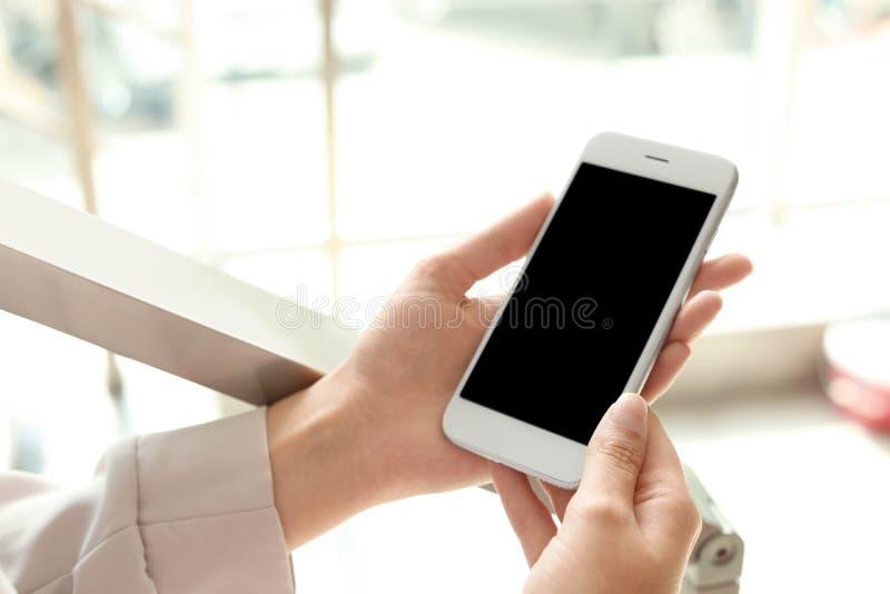 Mujer que sostiene smartphone con la pantalla en blanco fotos de archivo libres de regalías