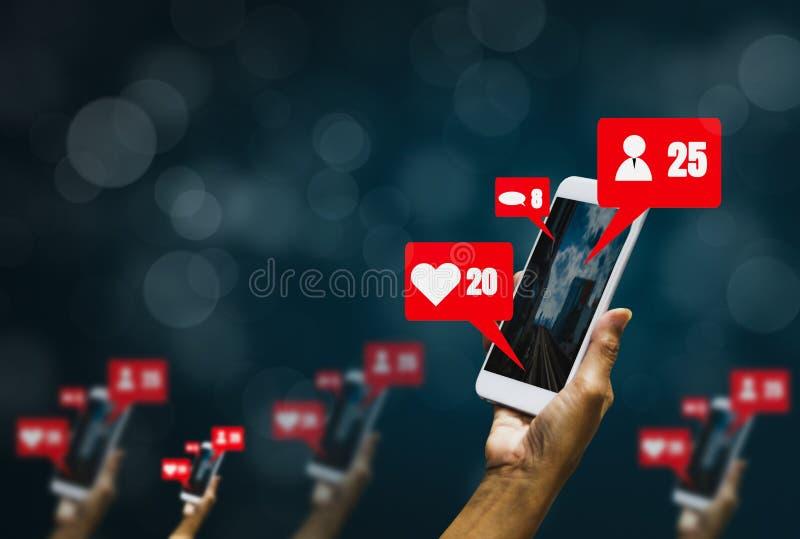 Mujer que sostiene smartphones y que disfruta de la distribución con los medios sociales, iconos que muestran sensaciones a travé foto de archivo libre de regalías