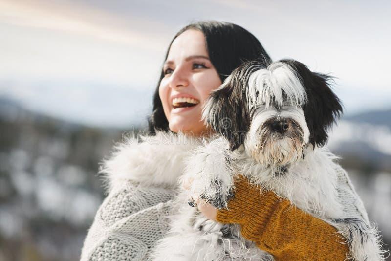 Mujer que sostiene su perrito del terrier tibetano en paisaje del invierno imágenes de archivo libres de regalías