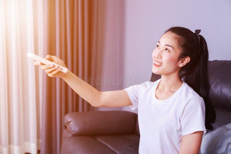 Mujer que sostiene un acondicionador de aire teledirigido en el sofá en casa fotos de archivo libres de regalías