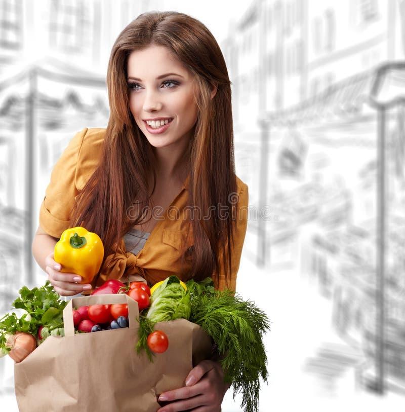 Mujer que sostiene un bolso lleno de alimento sano fotografía de archivo