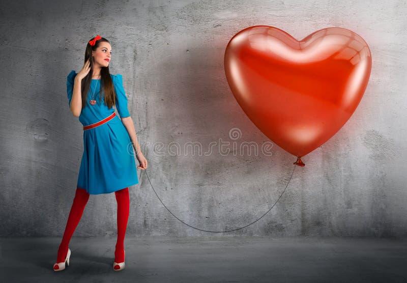 Mujer que sostiene un globo en forma de corazón fotos de archivo libres de regalías
