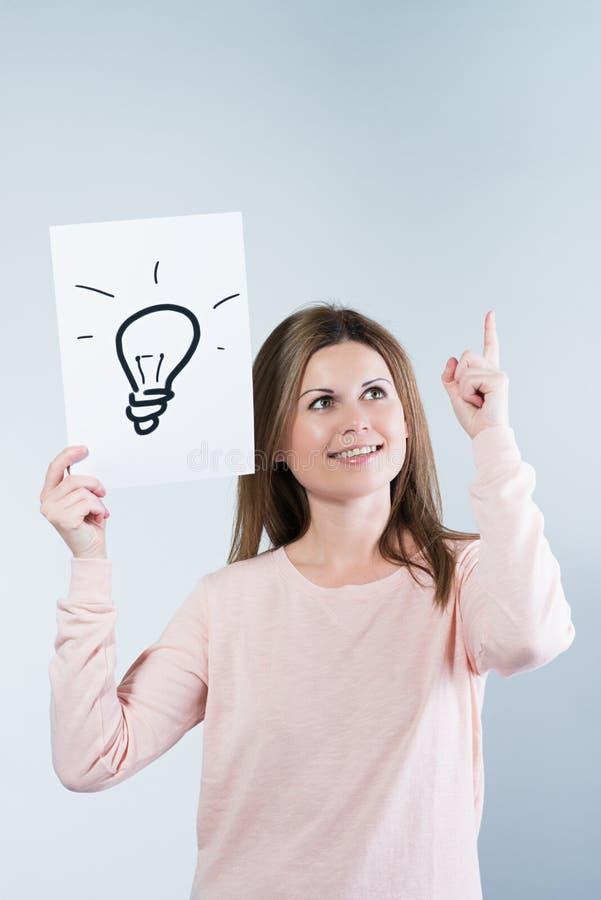 Mujer que sostiene un papel con las bombillas foto de archivo libre de regalías