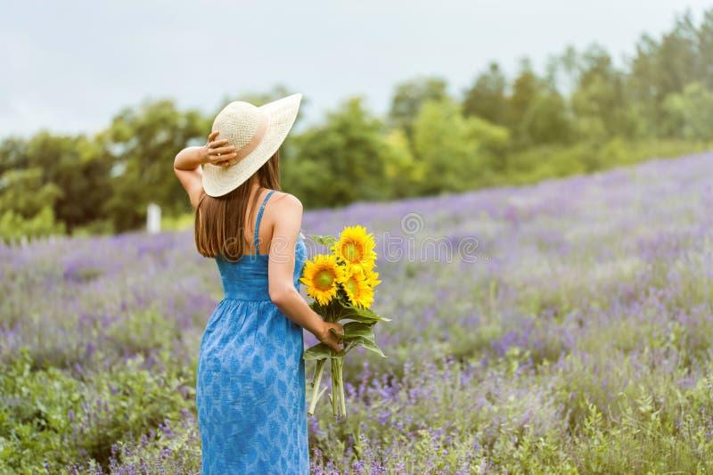 Mujer que sostiene un ramo de flor del sol fotos de archivo