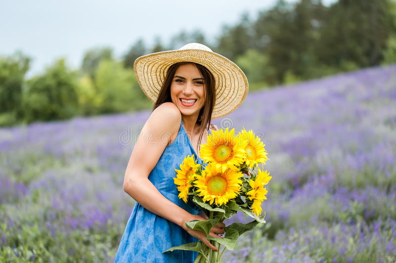 Mujer que sostiene un ramo de flor del sol, riendo foto de archivo libre de regalías