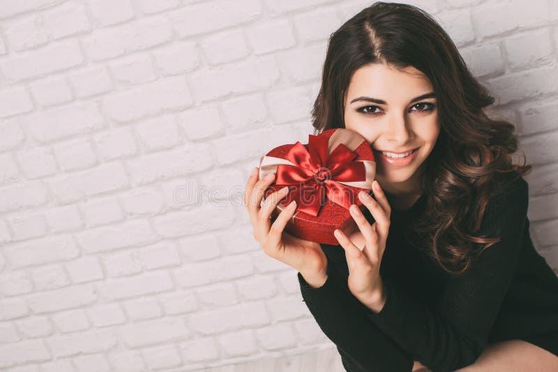 Mujer que sostiene un regalo en forma de corazón fotos de archivo