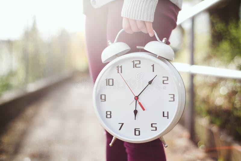 Mujer que sostiene un reloj fotografía de archivo