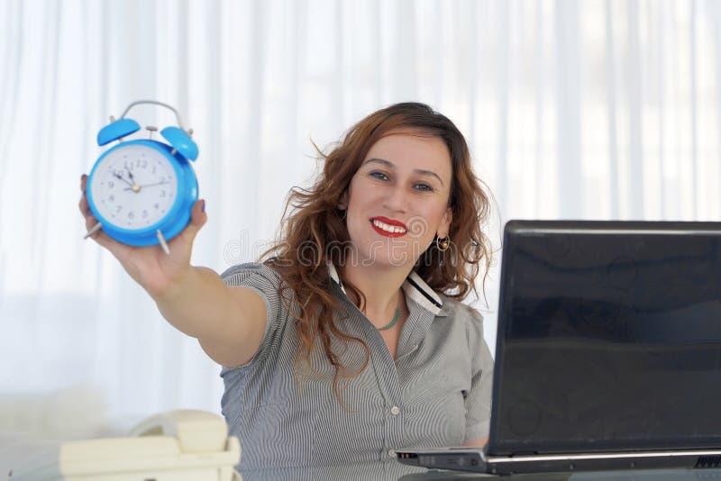 Mujer que sostiene un reloj La mujer pelirroja sostiene un despertador en su mano en el lugar de trabajo imagenes de archivo