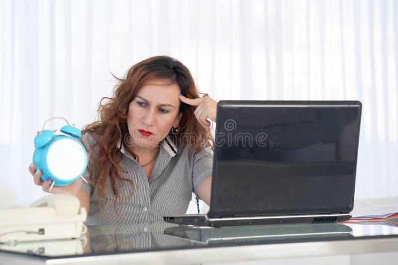 Mujer que sostiene un reloj La mujer pelirroja sostiene un despertador en su mano en el lugar de trabajo imagen de archivo libre de regalías