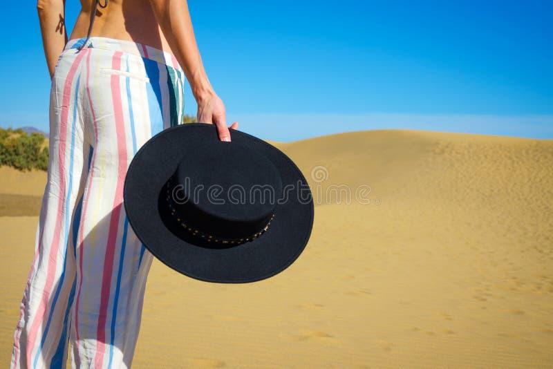 Mujer que sostiene un sombrero en su mano contra la perspectiva de dunas de arena y de un cielo azul Primer Moda fotografía de archivo libre de regalías