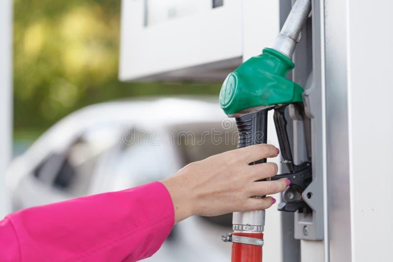 Mujer que sostiene un surtidor de gasolina en la estación de gasolina foto de archivo libre de regalías