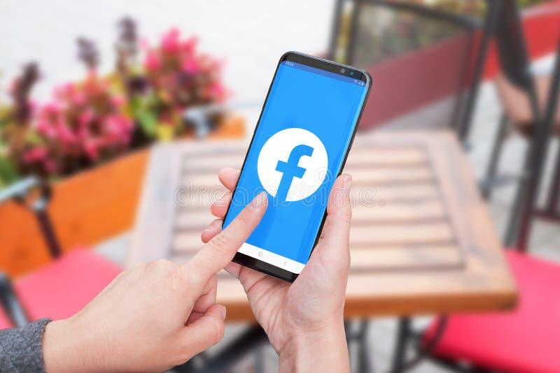Mujer que sostiene un teléfono elegante con el nuevo logotipo social de la red de Facebook imagenes de archivo
