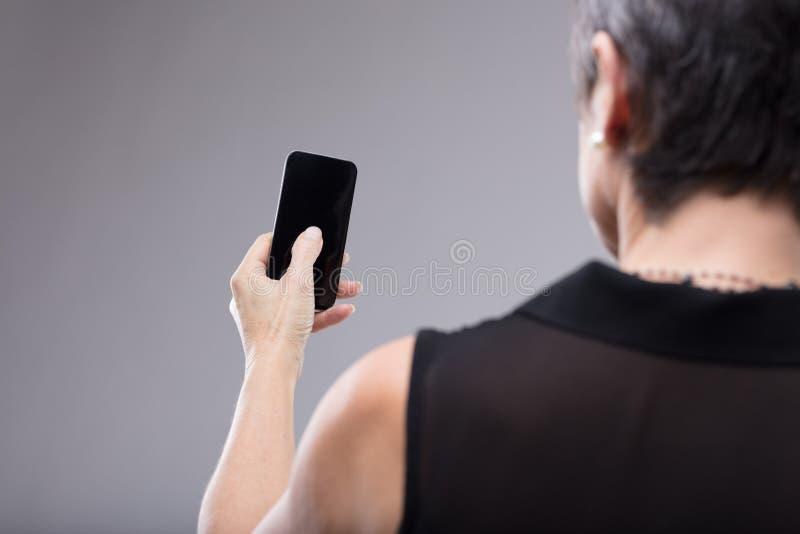 Mujer que sostiene un teléfono móvil negro en blanco foto de archivo libre de regalías