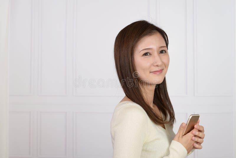 Mujer que sostiene un tel?fono elegante imagenes de archivo