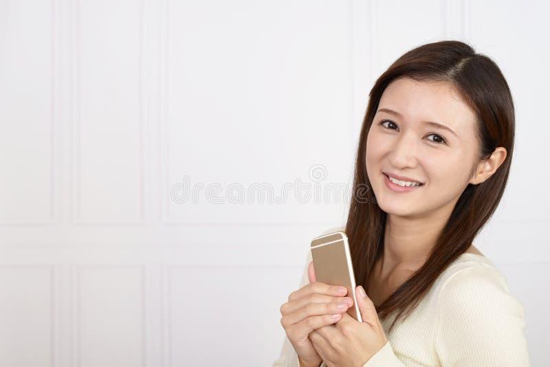 Mujer que sostiene un tel?fono elegante fotos de archivo libres de regalías