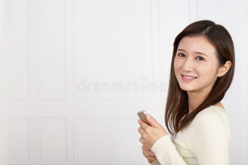 Mujer que sostiene un tel?fono elegante imagen de archivo
