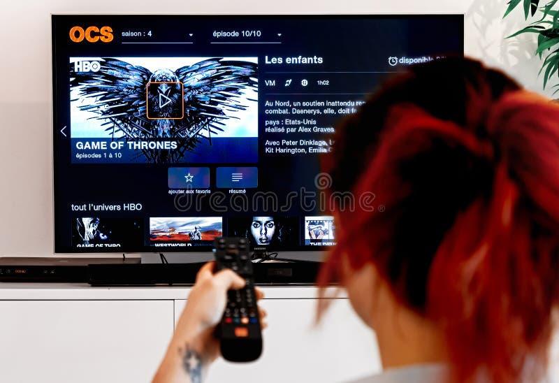 Mujer que sostiene un telecontrol de la TV y mirar el juego de tronos, una creación original de la industria de HBO imágenes de archivo libres de regalías