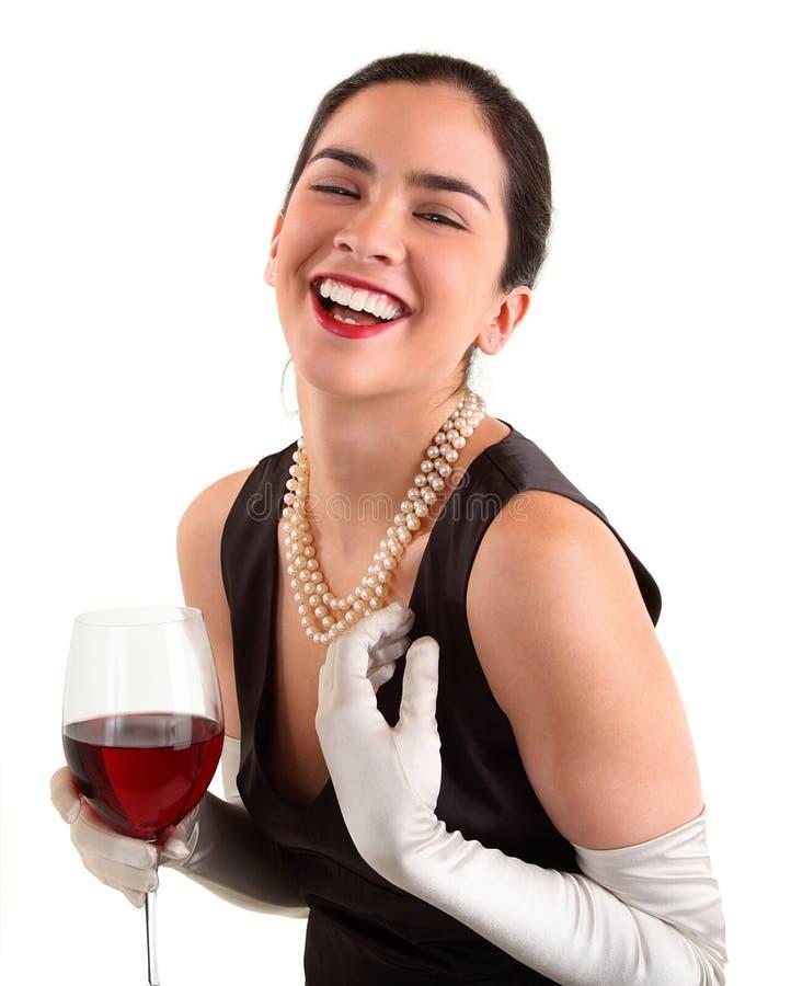 Mujer que sostiene un vidrio de vino y de risa fotos de archivo