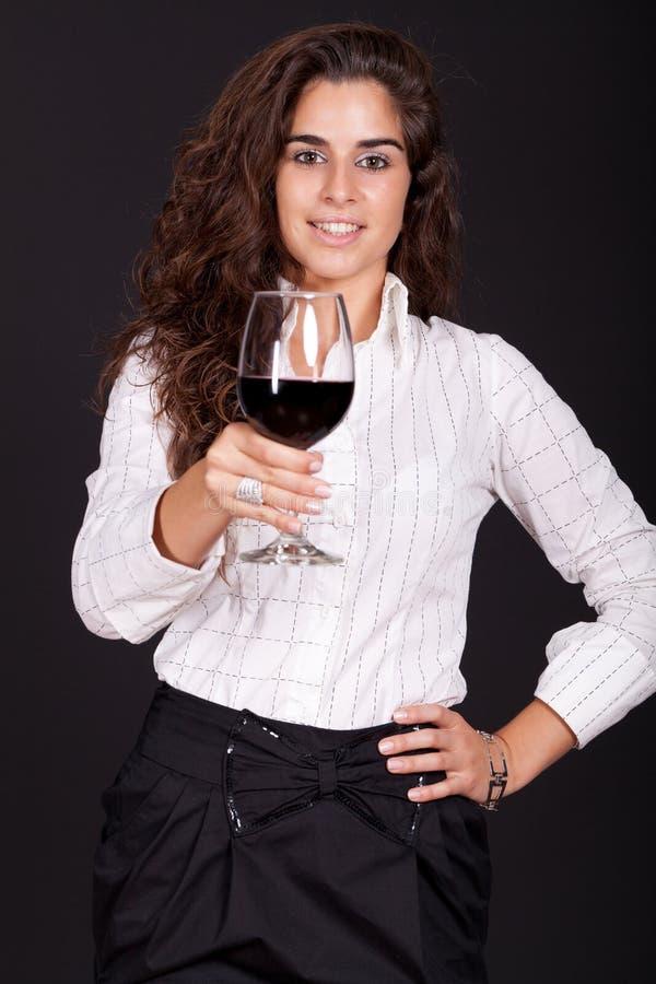 Mujer que sostiene un vidrio de vino y de sonrisa imagenes de archivo