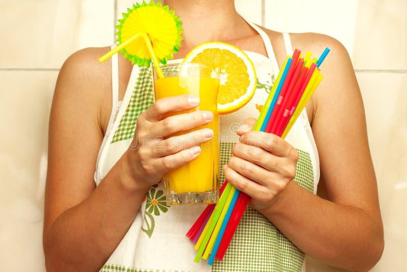 Mujer que sostiene un vidrio de zumo de naranja y de pajas de beber fotografía de archivo libre de regalías