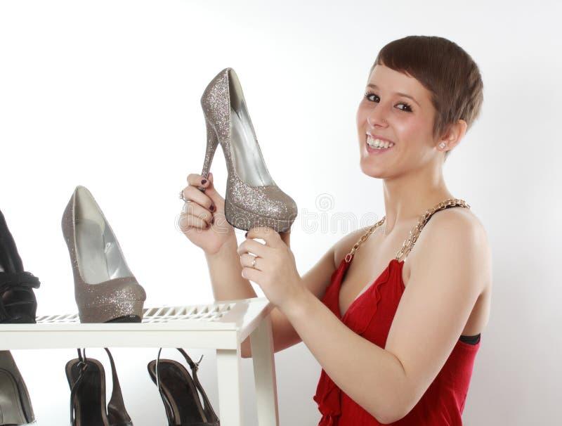 Mujer que sostiene un zapato agradable imagenes de archivo