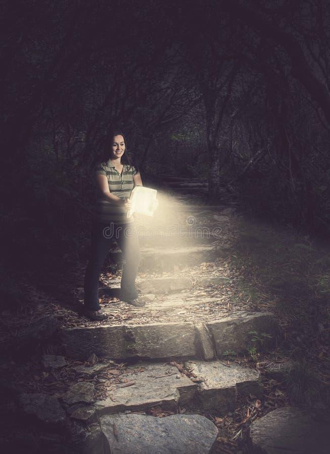 Mujer que sostiene una biblia que brilla intensamente en el bosque fotografía de archivo libre de regalías