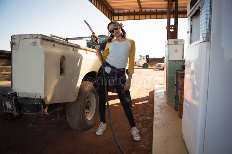 Mujer que sostiene una boca en la estación del surtidor de gasolina foto de archivo