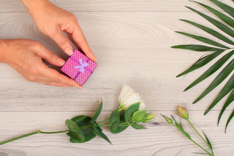 Mujer que sostiene una caja de regalo en las manos con las flores en los tableros imágenes de archivo libres de regalías