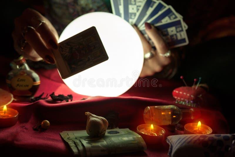 Mujer que sostiene una carta de tarot para la lectura futura imagen de archivo