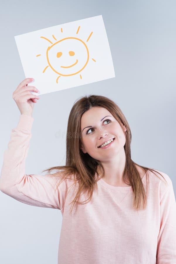 Mujer que sostiene una cartulina con un sol imagenes de archivo