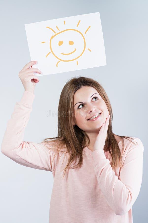Mujer que sostiene una cartulina con un sol foto de archivo