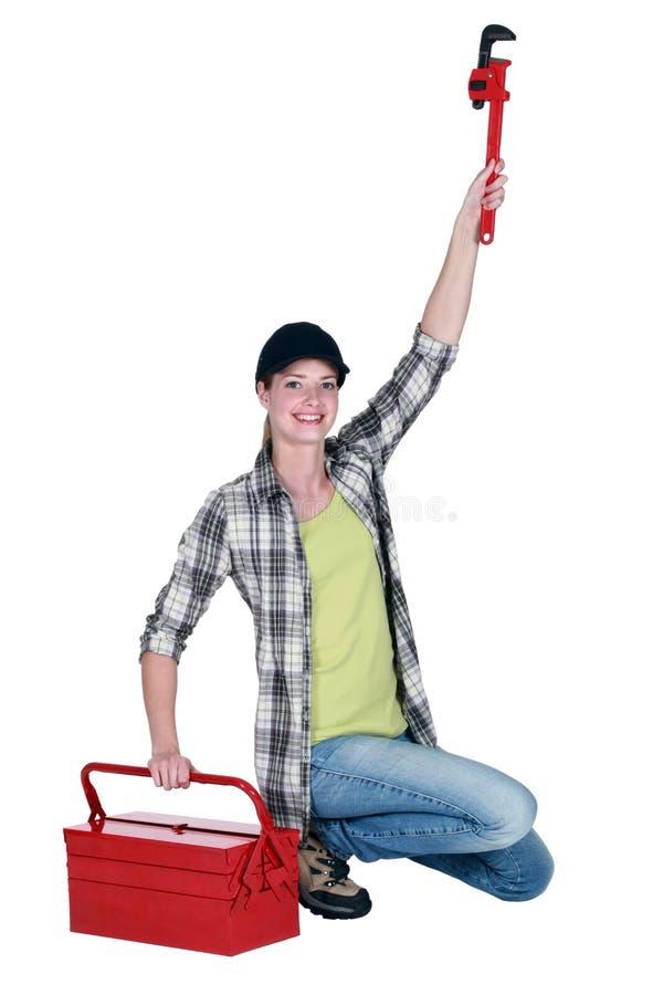 Mujer que sostiene una llave de tubo fotografía de archivo libre de regalías