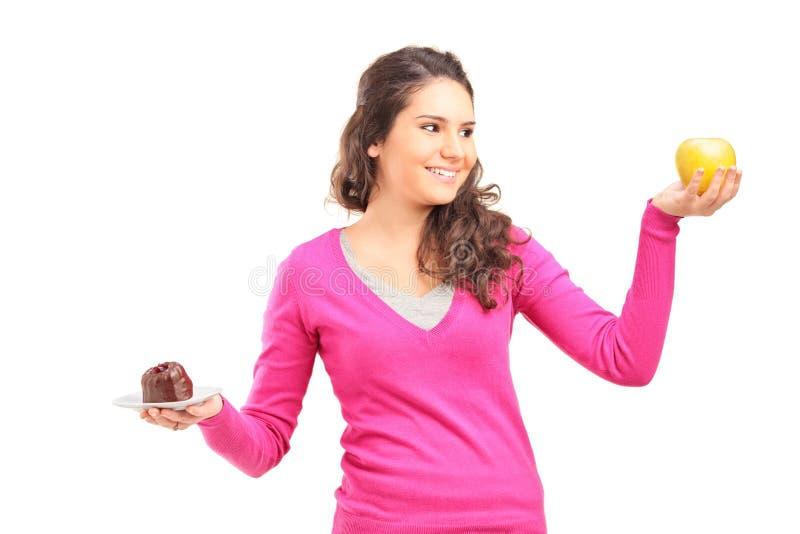 Mujer que sostiene una manzana y una torta y que intenta decidir cuál foto de archivo libre de regalías