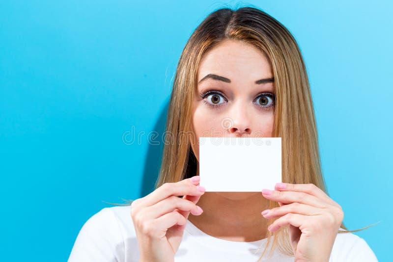 Mujer que sostiene una tarjeta en blanco del mensaje fotografía de archivo libre de regalías