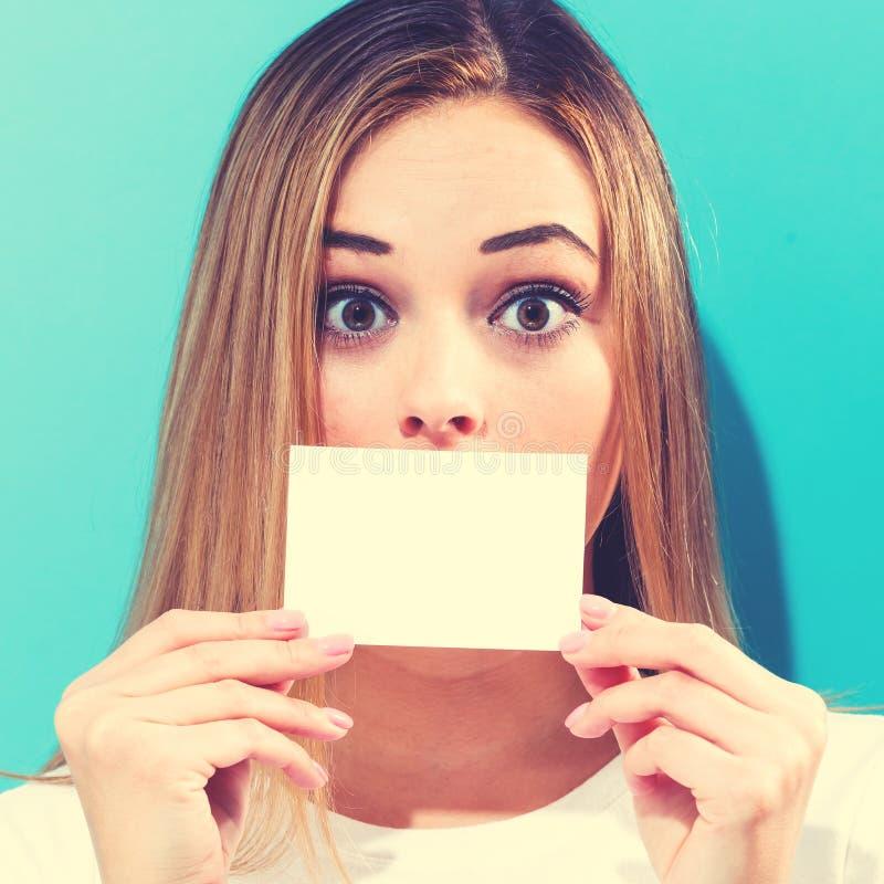 Mujer que sostiene una tarjeta en blanco del mensaje fotos de archivo libres de regalías