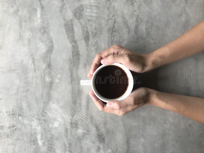 Mujer que sostiene una taza blanca de café caliente con sus ambas manos en la tabla del tablero del cemento imágenes de archivo libres de regalías