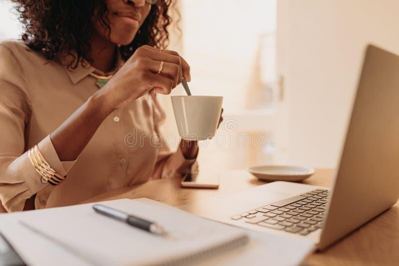 Mujer que sostiene una taza de café mientras que trabaja en el ordenador portátil en casa fotos de archivo