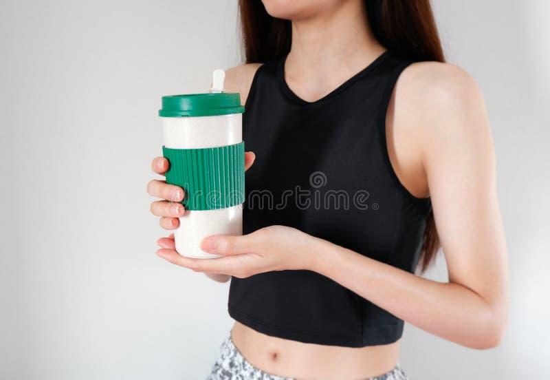 Mujer que sostiene una taza de caf? en manos con el fondo de las muchachas de los ejercicios Taza en blanco para el dise?o fotografía de archivo