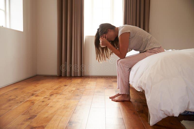 Mujer que sufre de la depresión que se sienta en cama y el griterío fotos de archivo