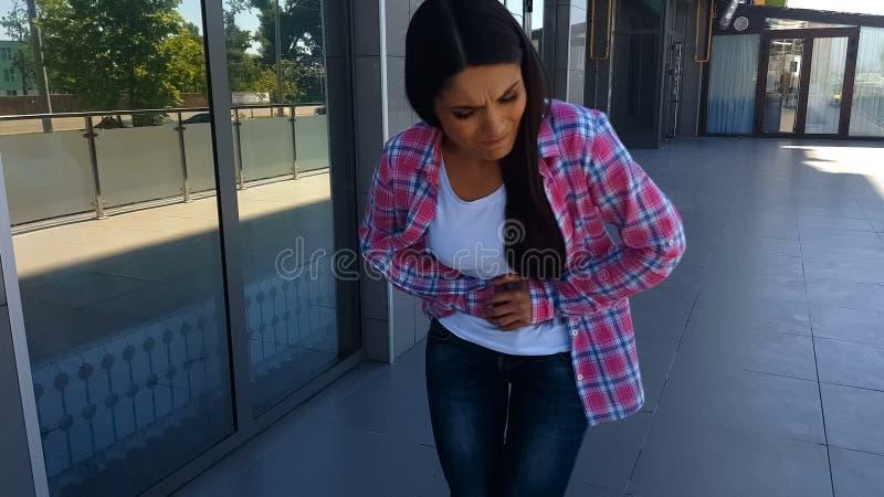 Mujer que sufre el aire libre abdominal fuerte del dolor, enfermedad de la gastritis, estómago foto de archivo libre de regalías