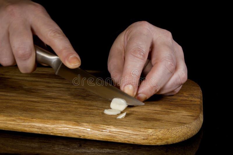 Mujer que taja el ajo con un cuchillo imagen de archivo