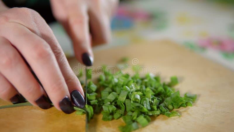 Mujer que taja las cebollas verdes en una tabla de cortar de madera fotografía de archivo