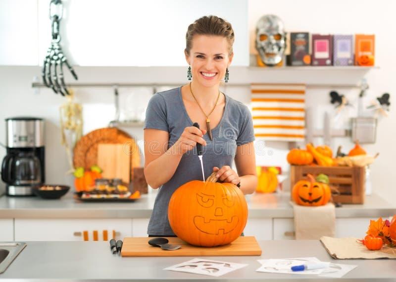 Mujer que talla una Jack-O-linterna de la calabaza para el partido de Halloween imagen de archivo libre de regalías
