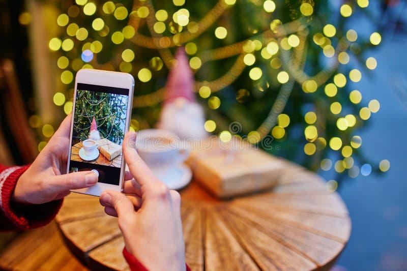 Mujer que tarda a foto PF su taza y regalo de Navidad de café imágenes de archivo libres de regalías