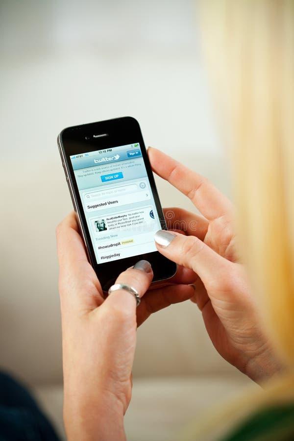 Mujer que tiene acceso al sitio web de Twitter en el iPhone 4 de Apple foto de archivo